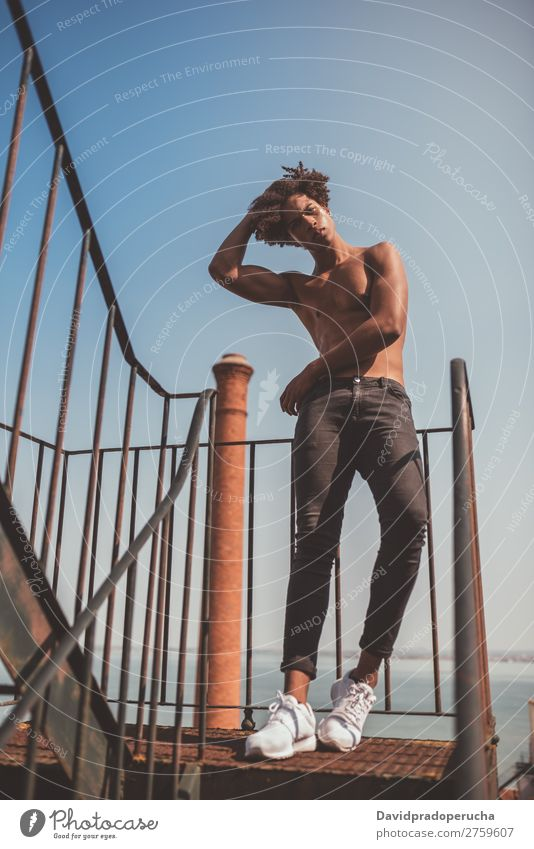 ein junger schwarzer Mann ohne Hemd auf der Treppe. Jugendliche Athlet nackt Torso Mensch Person gemischter Abstammung Afro-Look krause Haare Gesundheit Körper