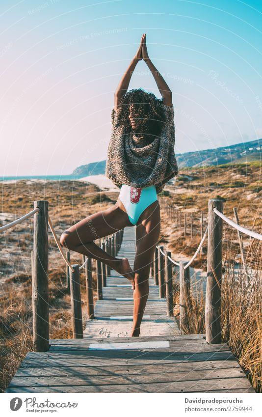 Junge schwarze Frau beim Yoga in einer hölzernen Fußgängerbrücke am Strand Hintergrundbild Bikini üben Brücke Küste