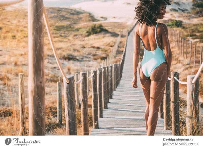 Junge Frau im Badeanzug, die in einer Holzsteg am Strand spazieren geht. Bikini Schwimmsport Anzug schwarz Brücke Hintergrundbild Küste krause Haare
