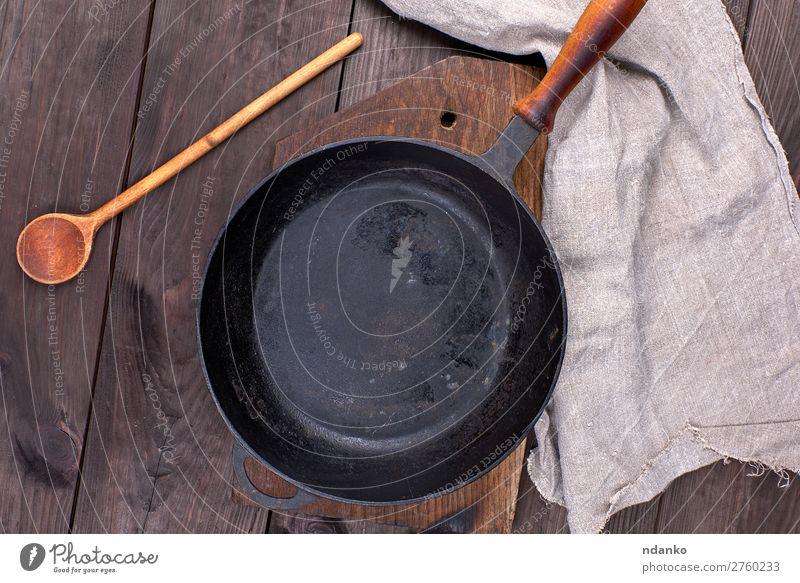 leere schwarze runde Pfanne Abendessen Löffel Tisch Küche Holz Metall alt dunkel oben Sauberkeit braun Hintergrund Holzplatte gießen Essen zubereiten