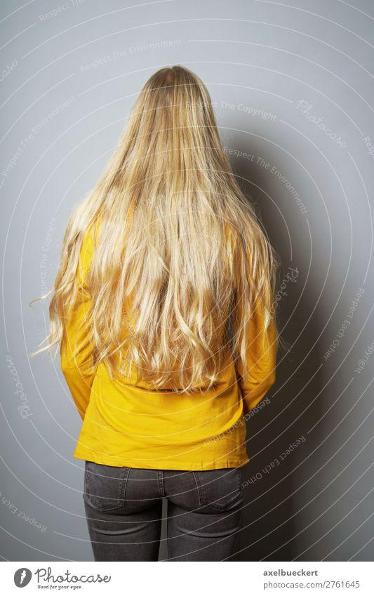 Frau mit langen blonden Haaren von hinten Mensch feminin Junge Frau Jugendliche Erwachsene 1 13-18 Jahre 18-30 Jahre Mauer Wand Jeanshose Haare & Frisuren