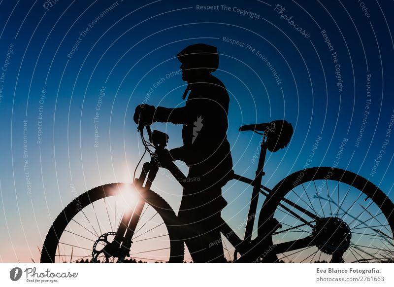 Silhouette eines Fahrradfahrers bei Sonnenuntergang. Sportkonzept. Lifestyle Erholung Freizeit & Hobby Abenteuer Sommer Berge u. Gebirge Fahrradfahren maskulin