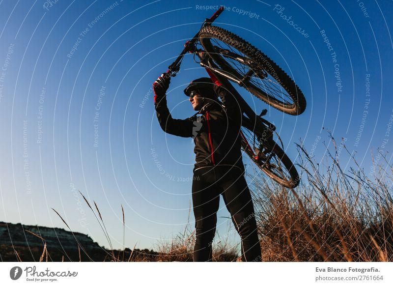 Radfahrer, der das Fahrrad bei Sonnenuntergang hält. Sport Lifestyle Erholung Freizeit & Hobby Abenteuer Sommer Berge u. Gebirge Fahrradfahren maskulin