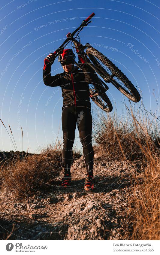 Radfahrer, der das Fahrrad bei Sonnenuntergang hält. Sportkonzept. Lifestyle Erholung Freizeit & Hobby Abenteuer Sommer Berge u. Gebirge Fahrradfahren maskulin