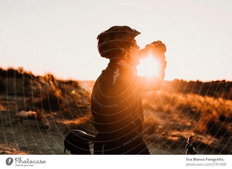 Radfahrer trinken bei Sonnenuntergang Wasser auf dem Fahrrad. Sport Getränk Trinkwasser Lifestyle Freizeit & Hobby Abenteuer Sommer Berge u. Gebirge