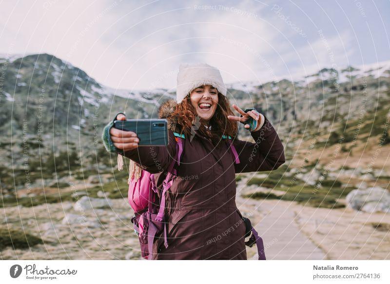 Brünettes Mädchen mit ihrem Rucksack macht sie ein Foto. Lifestyle Glück Ferien & Urlaub & Reisen Tourismus Ausflug Abenteuer Freiheit Berge u. Gebirge Telefon