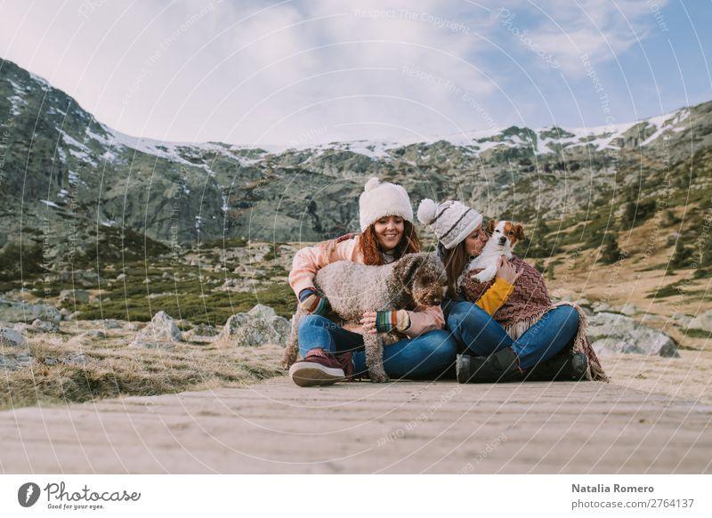 zwei Freunde spielen mit ihren Hunden auf der Wiese. Lifestyle Stil Freude Glück schön Freizeit & Hobby Spielen Abenteuer Berge u. Gebirge Sport Frau Erwachsene