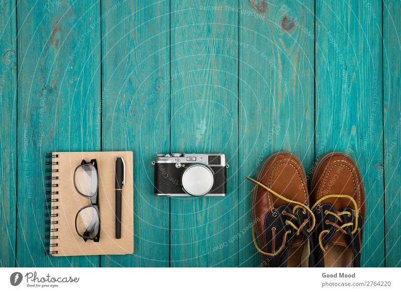 Schuhe, Notizblock, Kamera, Brille auf Holzschreibtisch Ferien & Urlaub & Reisen Ausflug Schreibtisch Tisch Fotokamera Junge Mann Erwachsene Mode Bekleidung