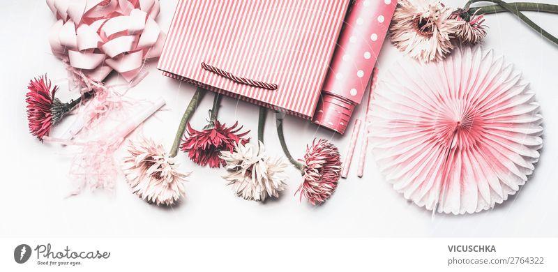 Zusammenstellung von rosa Accessoires für weibliche Feiertage: Muttertag, Frauentag, Geburtstag oder Hochzeit. Papier-Einkaufstasche mit Blumen, Papier, Partyfächer und Band auf weißem Hintergrund, Ansicht von oben