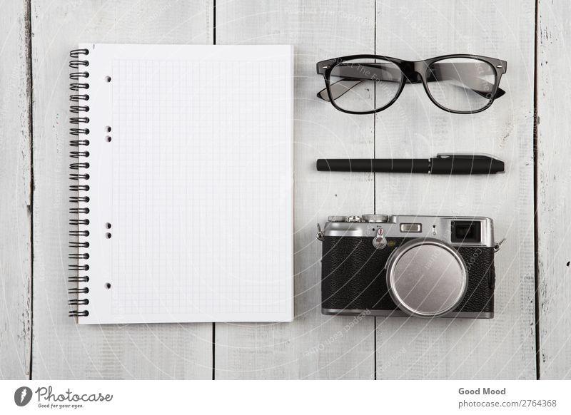 Arbeitsplatz mit Notizblock, Kamera, Stift und Brille lesen Ferien & Urlaub & Reisen Schreibtisch Tisch Büro Business Fotokamera Musiknoten Papier Schreibstift