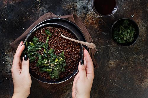 Eintopf mit schwarzen Linsen und Gemüse Vegetarische Ernährung Teller Löffel Hand dunkel oben Hülsenfrüchte schmoren Beluga Spinat Vegane Ernährung essen