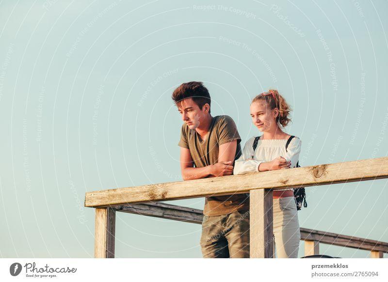 Lächelnde junge Frau und Mann, die auf einem Pier über dem Meer sitzen. Lifestyle Freude Glück Freizeit & Hobby Ferien & Urlaub & Reisen Sommer Mensch Junge