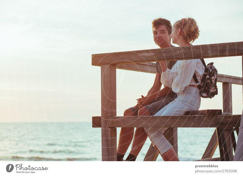 Ein paar junge Frauen und Männer sitzen auf einem Pier über dem Meer. Lifestyle Freude Glück Freizeit & Hobby Ferien & Urlaub & Reisen Sommer Mensch Junge Paar