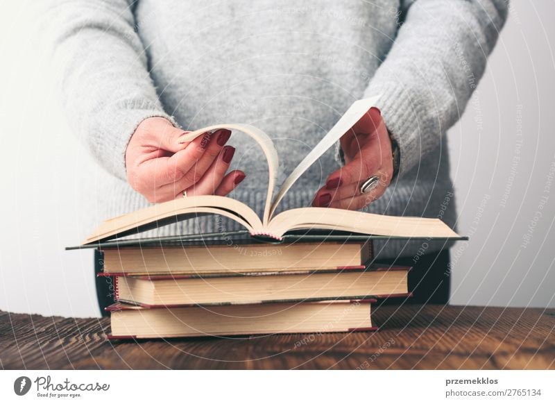 Frau blättert Seiten des Buches auf dem Tisch im Antiquariat um. Lifestyle kaufen Erholung Freizeit & Hobby lesen Schule lernen Mensch Erwachsene Jugendliche 1
