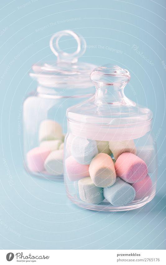 Ein mit bunten Marshmallows gefülltes Glas auf schlichtem Hintergrund. Dessert Süßwaren Ernährung Essen Diät Tisch hell lecker blau Farbe Bonbon farbenfroh