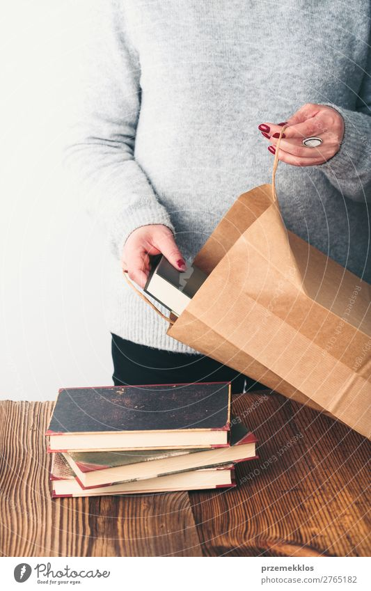 Junge Frau, die alte Bücher in die Papiertasche im Antiquariat bringt. Lifestyle kaufen Erholung Freizeit & Hobby lesen Schule lernen Mensch Erwachsene