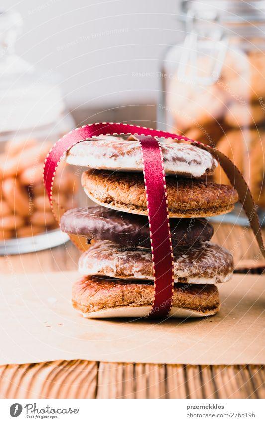 Ein paar Lebkuchenplätzchen in rotem Band auf Holztisch verpackt. Dessert Ernährung Essen Diät Glück Tisch Schnur genießen lecker braun Weihnachten backen