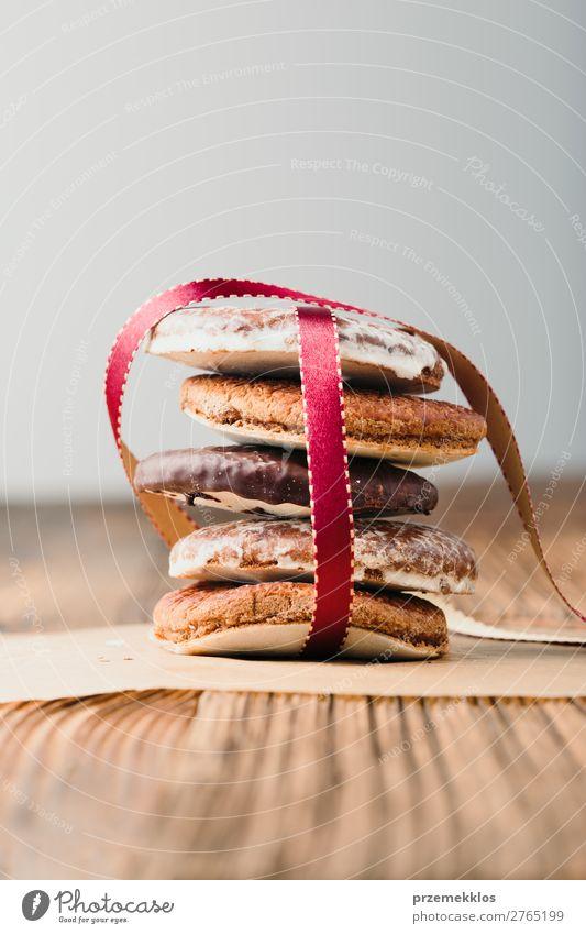 Ein paar Lebkuchenplätzchen in rotem Band auf Holztisch verpackt. Dessert Ernährung Essen Diät Tisch Schnur genießen lecker braun backen Bäckerei Biskuit