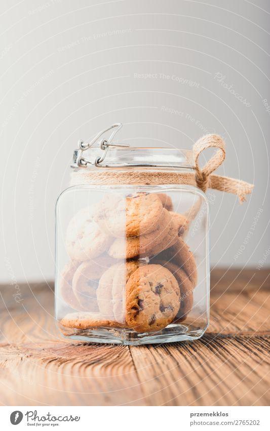 Großes Glas mit Haferplätzchen gefüllt, das auf einem Holztisch steht. Dessert Ernährung Essen Diät Lifestyle Tisch genießen lecker braun backen Bäckerei