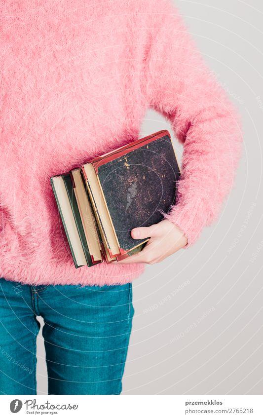 Junges Mädchen, das ein paar Bücher hält. Lifestyle Erholung Freizeit & Hobby lesen Schule lernen Mensch Frau Erwachsene Jugendliche 1 Buch Bibliothek Pullover