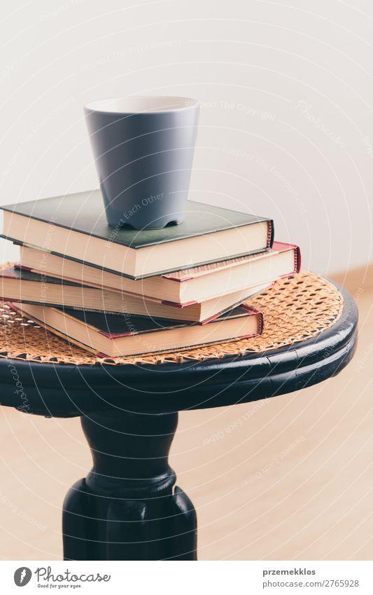 Ein paar Bücher mit einer Tasse Kaffee auf dem Stuhl Becher Lifestyle Erholung Freizeit & Hobby lesen Tisch Buch genießen heiß Geborgenheit bequem gemütlich