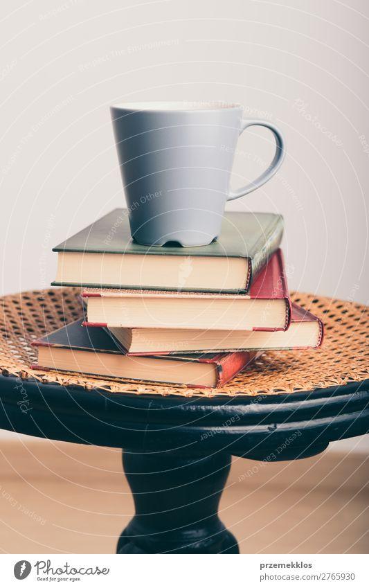 Ein paar Bücher mit einer Tasse Kaffee auf dem Stuhl Becher Lifestyle Erholung Freizeit & Hobby lesen Tisch Buch genießen braun Geborgenheit bequem gemütlich