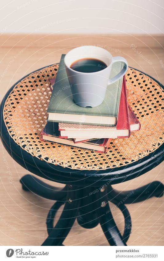 Ein paar Bücher mit einer Tasse Kaffee auf dem Stuhl Becher Lifestyle Erholung Freizeit & Hobby lesen Tisch Buch genießen Geborgenheit bequem gemütlich trinken