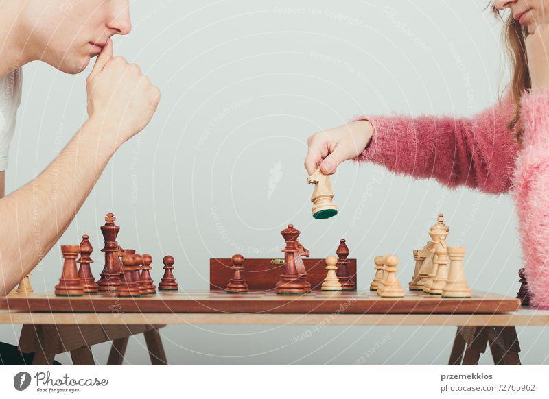 Mädchen und Junge spielen zu Hause Schach. Mädchen bewegt ihre Figur Lifestyle Freizeit & Hobby Spielen Erfolg Mensch Frau Erwachsene Mann genießen klug schwarz