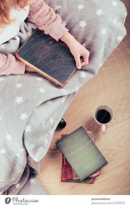 Mädchen genießt das Lesen eines Buches und trinkt zu Hause Kaffee. Lifestyle Erholung Freizeit & Hobby lesen Kind Mensch Frau Erwachsene Wärme blond genießen