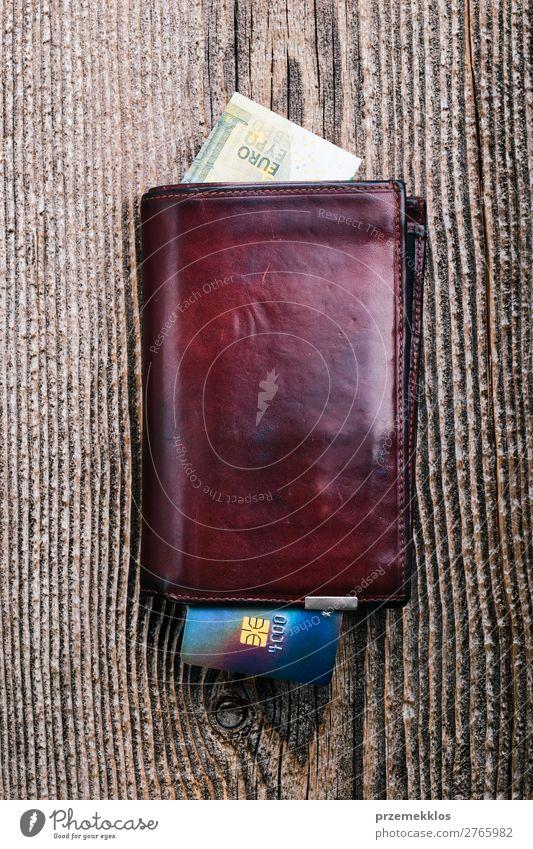 Ledergeldbörse mit Euro-Banknoten, Kreditkarte auf Holzschreibtisch Geld Tisch Erfolg Kapitalwirtschaft oben braun Geldscheine Postkarte Bargeld Belastung