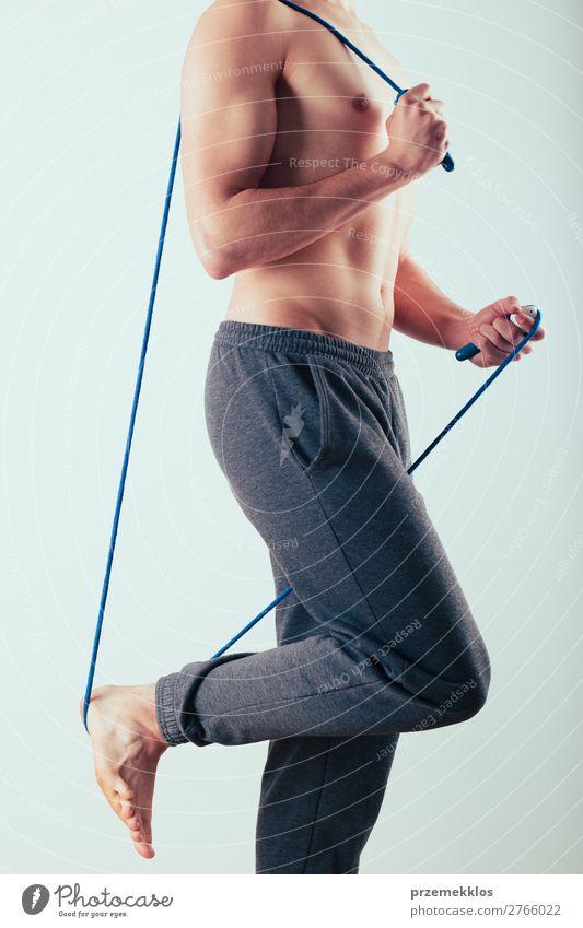 Junger Mann hält ein Springseil und macht Übungen zu Hause. Lifestyle Sport Seil Mensch Erwachsene Fitness springen oben Aktion Kaukasier üben passen Sporthalle