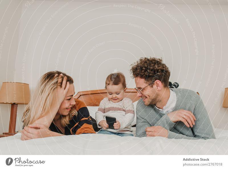 Fröhliches Paar mit Kind im Bett Familie & Verwandtschaft Mutter Vater PDA Spielen heiter Mensch Hotel Raum Schlafzimmer heimwärts Innenarchitektur Möbel