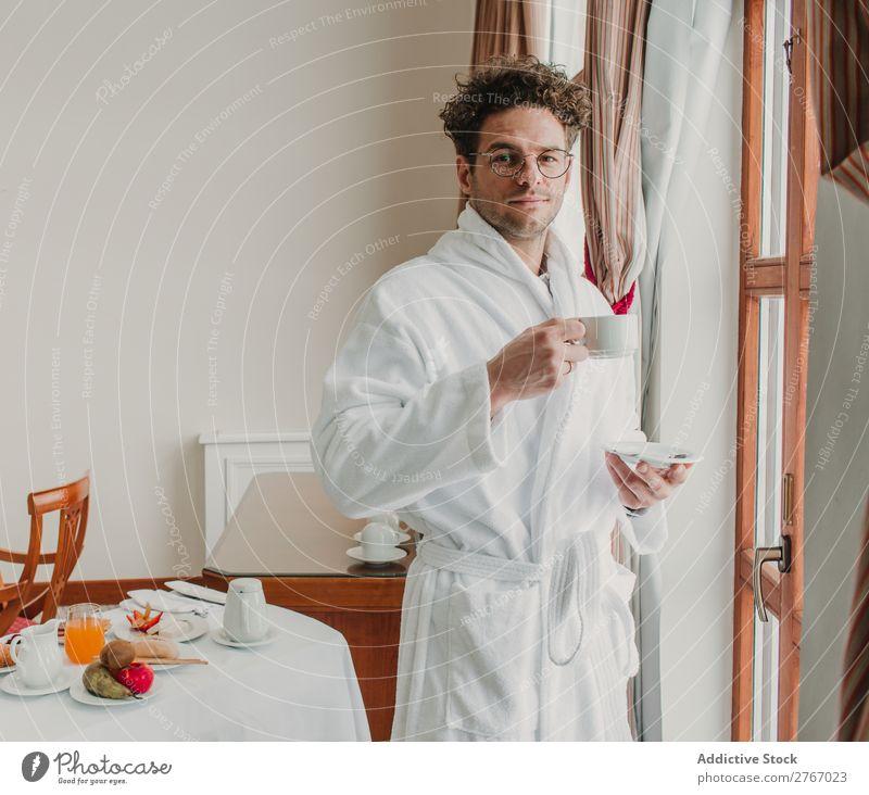 Mann im Bademantel mit Tasse selbstbewußt Stil Keramik Fenster trinken Frühstück Zimmerservice Hotel Raum Schlafzimmer heimwärts Innenarchitektur Möbel Wohnung