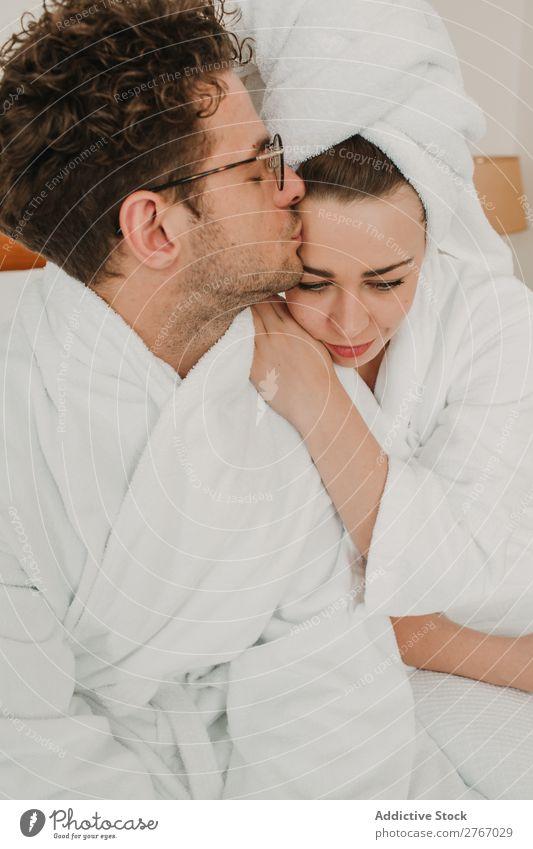 Ein glückliches Paar, das sich auf dem Bett umarmt. Bademantel umarmend Kuscheln Augen geschlossen Hotel Raum Schlafzimmer heimwärts Innenarchitektur Möbel