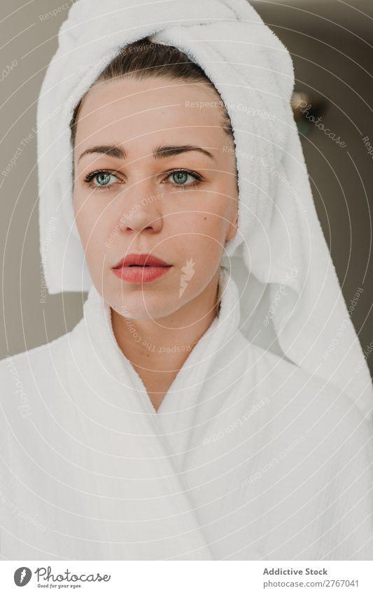 Nachdenkliche Frau, die im Bademantel posiert. Handtuch heiß selbstbewußt Jugendliche hübsch Wegsehen stehen Fürsorge Hotel Raum heimwärts Innenarchitektur