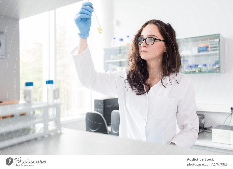 Frau, die auf das Reagenzglas schaut. Labor Arbeit & Erwerbstätigkeit Wissenschaften Reaktionen u. Effekte beobachten Mensch forschen Wissenschaftler Medikament