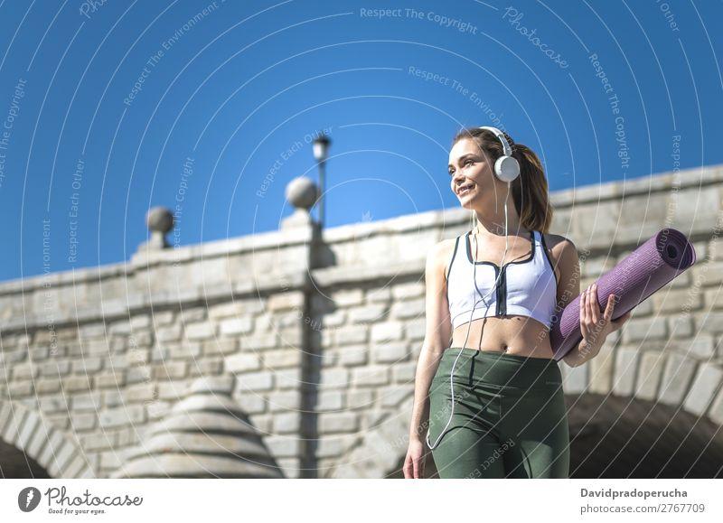 Frau geht mit Yoga und Pilates Matte und hört Musik. Lifestyle schön Körper Wellness Erholung Meditation Sport Mensch Erwachsene Natur Wärme Park brünett