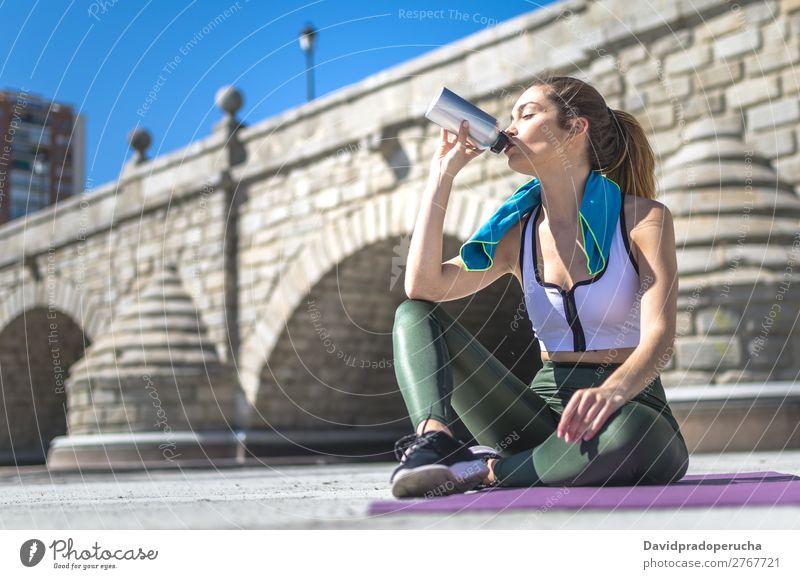 Frau ruht sich aus und trinkt Wasser mit Handtuch nach dem Training. Lifestyle schön Körper Erholung Meditation Sport Yoga Mensch Erwachsene Natur Wärme Park