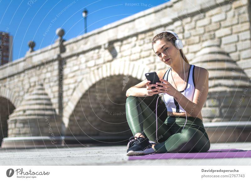 Frau ruht sich aus und hört Musik mit dem Handy, während sie trainiert. Lifestyle schön Wellness Erholung Meditation Sport Yoga Mensch Erwachsene Natur Wärme