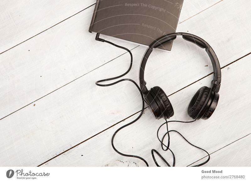 Hörbuchkonzept mit Black Book und Kopfhörern Freizeit & Hobby Spielen lesen Musik Schule lernen Headset Technik & Technologie Medien Buch Bibliothek Papier Holz