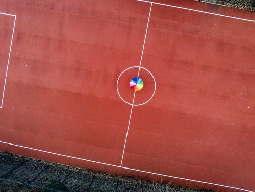 Regenbogeschirm auf rotem Spielfeld Ferien & Urlaub & Reisen Tourismus Ausflug Freiheit Sightseeing Städtereise Sportstätten Fußballplatz Hauptstadt
