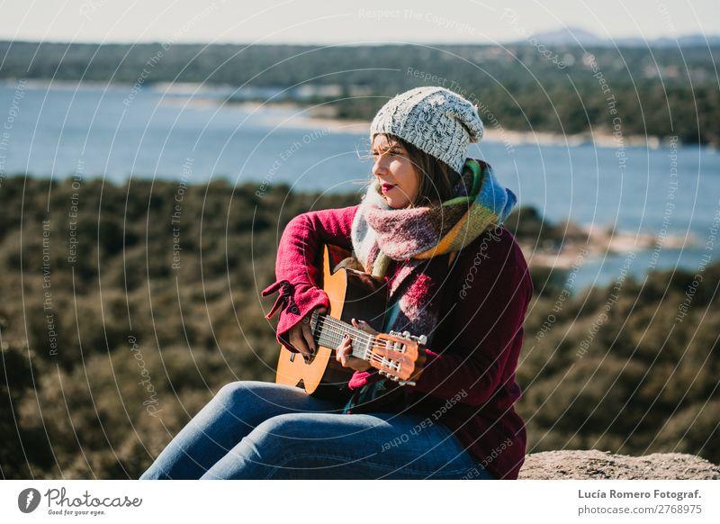 Frau, die im Freien Gitarre spielt. Lebensstil Lifestyle Freude Glück Erholung Freizeit & Hobby Spielen Ferien & Urlaub & Reisen Winter Musik Mensch feminin