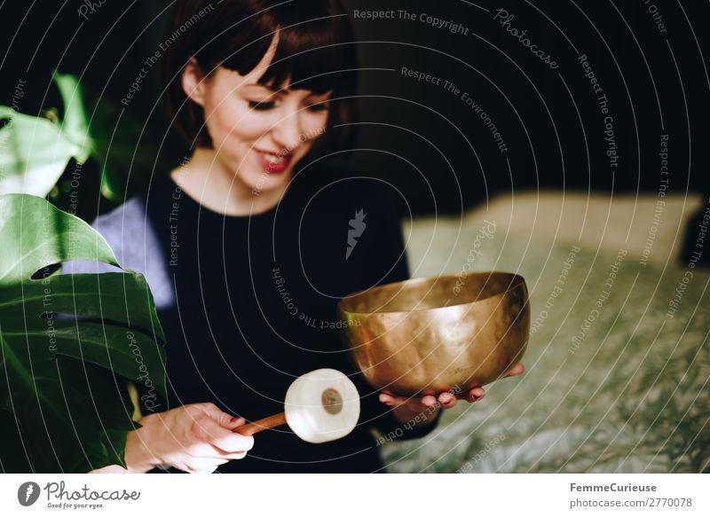 Mindfulness - Woman with singing bowl in her cozy home feminin Frau Erwachsene 1 Mensch 18-30 Jahre Jugendliche 30-45 Jahre Zufriedenheit Erholung Gelassenheit