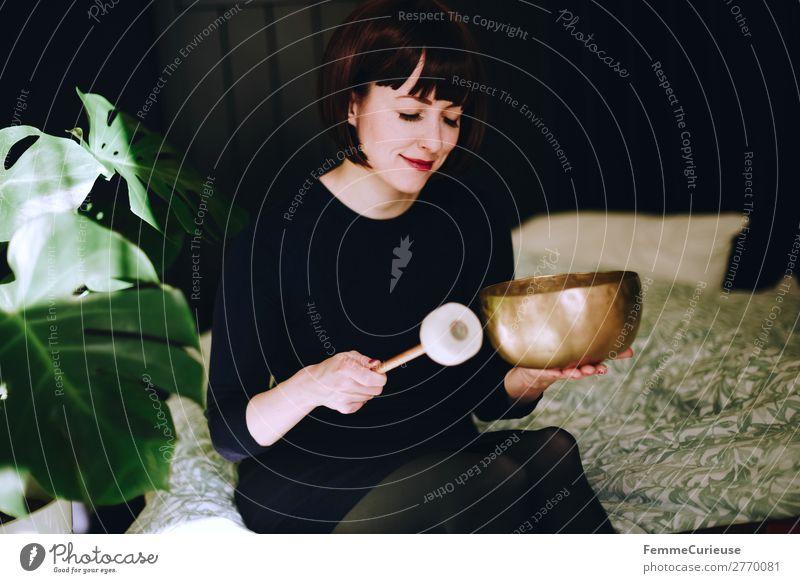 Mindfulness - Woman with singing bowl in her cozy home Lifestyle feminin Frau Erwachsene 1 Mensch 18-30 Jahre Jugendliche 30-45 Jahre Zufriedenheit Erholung