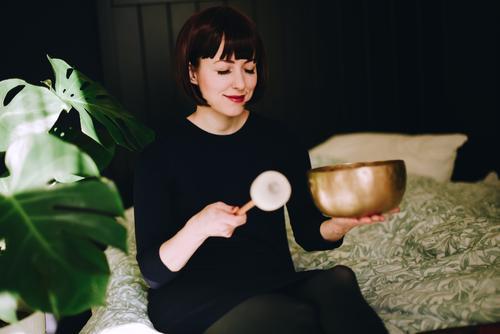 Mindfulness - Woman with singing bowl in her cozy home Frau Mensch Jugendliche Erholung ruhig Gesundheit 18-30 Jahre Erwachsene feminin Häusliches Leben