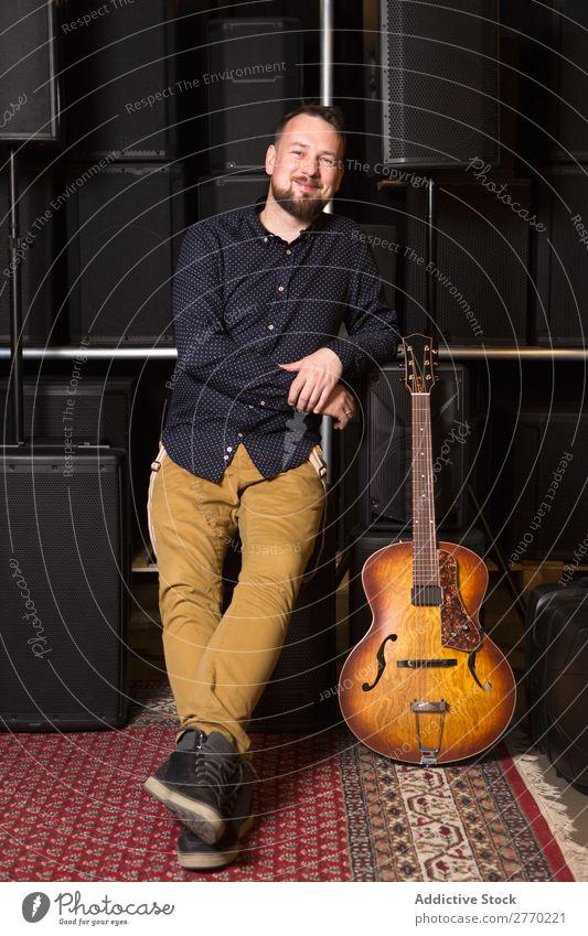 Gitarrist auf Gitarrencombo sitzend Mann kaufen Blick in die Kamera Gitarrenkombination Verkäufer Kunde Reihen Musical akustisch Gerät Mensch Business Porträt