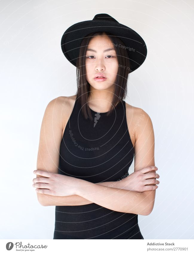 Junge asiatische Frau mit verschränkten Armen Stil modisch Hut schön Mode Beautyfotografie Jugendliche Model Porträt attraktiv elegant Glamour