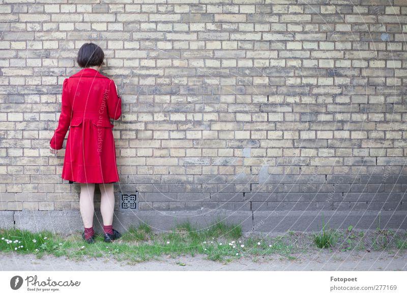Gegen die Wand feminin Junge Frau Jugendliche 1 Mensch 18-30 Jahre Erwachsene Mauer Mantel schwarzhaarig berühren stehen rot ruhig Enttäuschung Einsamkeit Scham