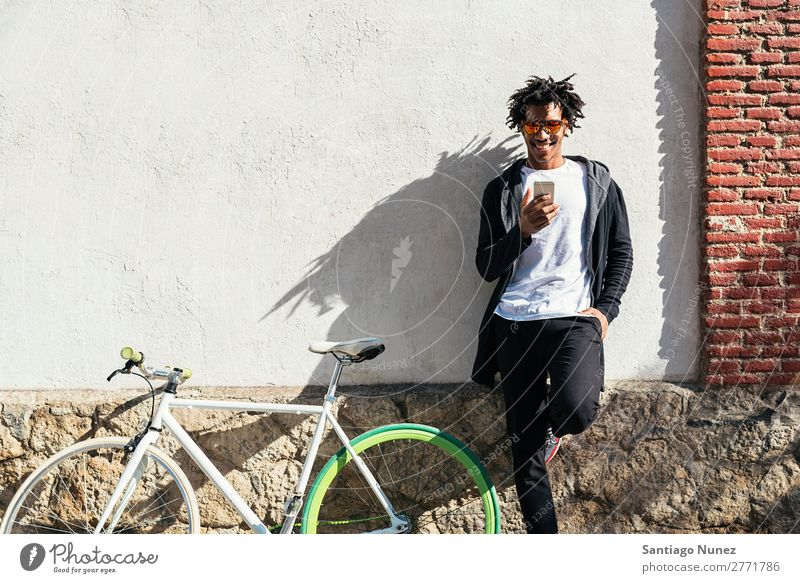 Afrojunger Mann mit Handy und festem Fahrrad. Jugendliche Afrikanisch schwarz Mulatte Afro-Look Mobile Fixie Telefon Lifestyle stehen Fahrradfahren benutzend