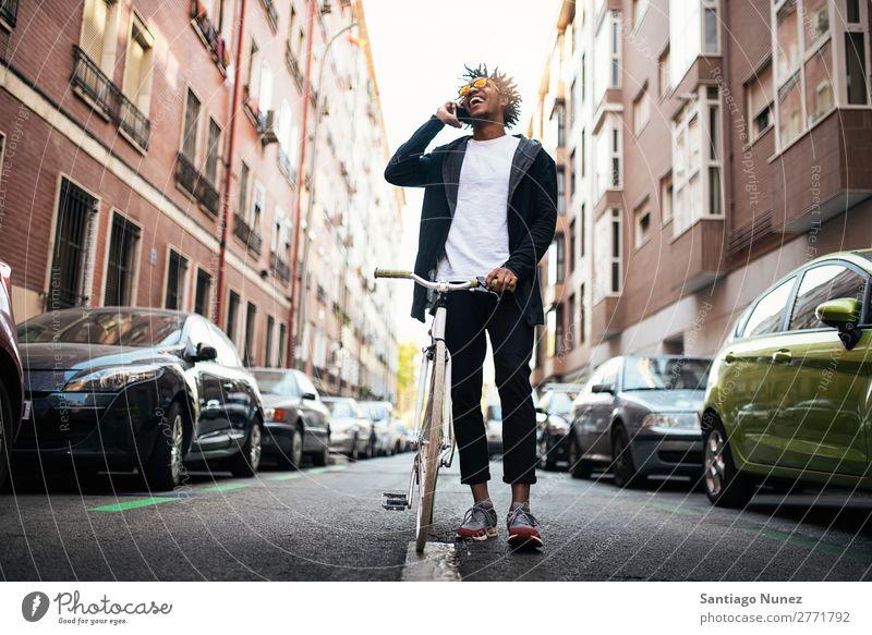 Gutaussehender junger Mann mit Handy und festem Fahrrad. Jugendliche Afrikanisch schwarz Mulatte Afro-Look Mobile Fixie Telefon Lifestyle stehen Fahrradfahren